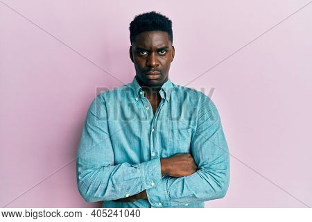 Handsome black man wearing casual clothes skeptic and nervous, disapproving expression on face with crossed arms. negative person.