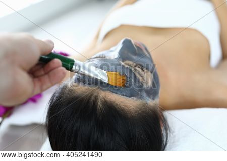 Beautician Applying Black Mask To Clients Face In Beauty Salon. Facial Treatment Concept
