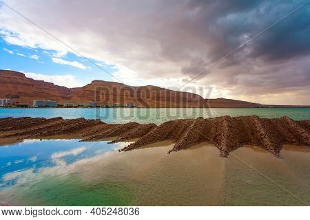 Legendary Dead Sea. The smooth surface of the very salty sea water reflects the sky and clouds. Low winter clouds are reflected in the green sea water. Israel