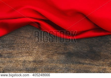 Red Satin Fabric On Brown Wood Background. Valentines Day Background