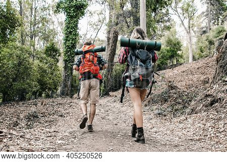 Rear View Of Hikers Walking On Mountainous Trail. Caucasian Hikers Or Traveler With Backpacks Having
