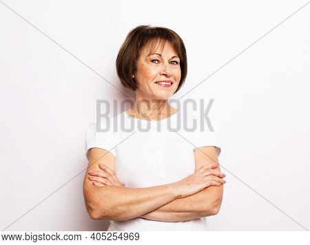 Old people, emotion and modern lifestyle concept. Portrait of senior happy woman with cute smile standing with his arms crossed over white background