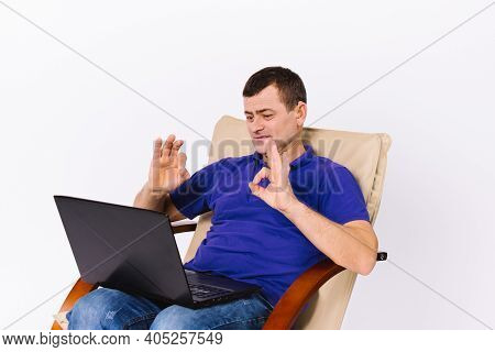 A Deaf Senior Man With A Laptop Shows A Sign To The Camera That Everything Is Fine While Sitting In