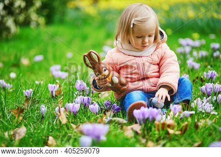 Cute Little Girl Holding Chocolate Bunny And Playing Egg Hunt On Easter. Toddler Looking For Colorfu