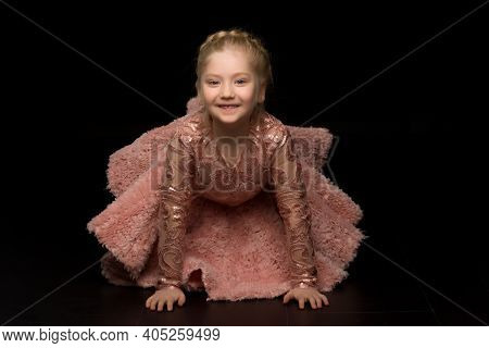 A Beautiful Little Girl Is Kneeling In The Studio On A Black Background. Concept Poems Fashion.