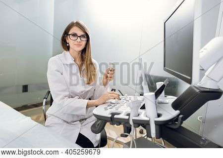 Smiling Pleasant Pretty Woman Doctor With Ultrasound Transducer In Hand, Working On Modern Ultrasoun