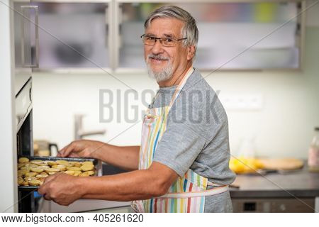 Senior man prepares healthy version of potatoes in the oven