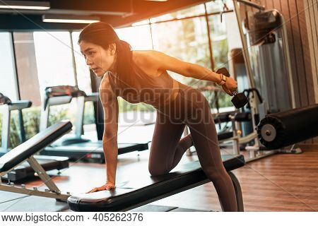 Young Beautiful Slim Woman Doing Exercises With Dumbbell In Gym