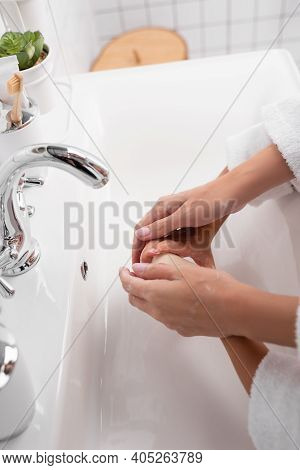 Cropped View Of Mother And Child Washing Hands With Sop In Bathroom