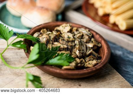 closeup of an earthenware plate with some sliced mushrooms cooked with garlic and parsley on a gray rustic wooden table next to some plates with some cooked baby corns and some buns in the background
