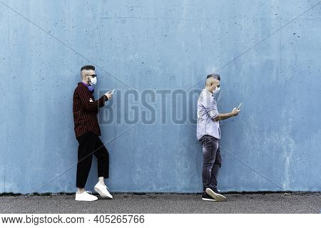 Cool Men In A Line Using Mobile Phones While Keeping Social Distance And Wearing Face Medical Mask -