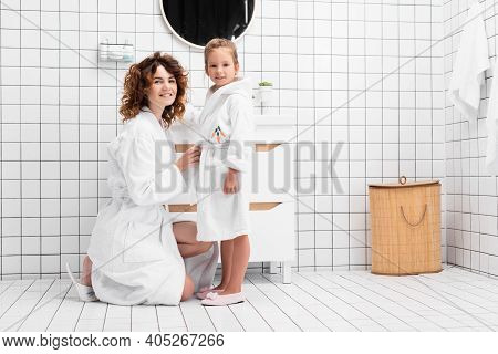 Mother And Daughter In Bathrobes Smiling At Camera In Bathroom