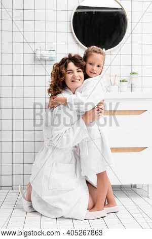 Daughter And Mother In Bathrobes Hugging In Bathroom
