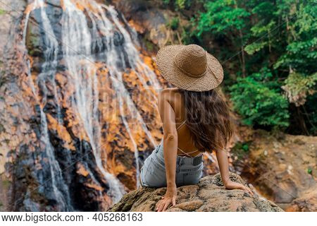 A Beautiful Girl Is Resting In The Jungle Near A Waterfall. Na Muang Waterfall At Samui Tourist Dest
