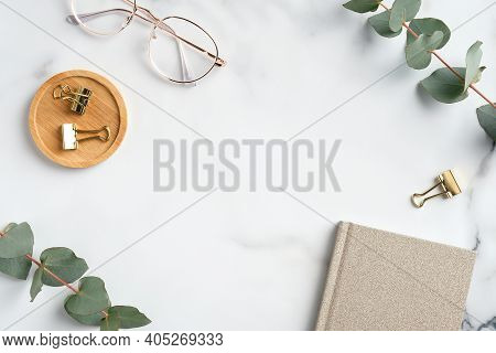 Marble Office Desk Table With Notebook, Glasses, Eucalyptus Branches. Elegant Rustic Feminine Worksp