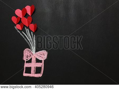 Pink Gift Box Drawn On A Black Board With Red Paper Hearts. Copy Space. Gifts Concept. Valentine's D