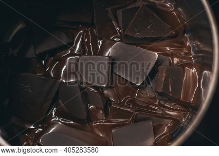 Melted Dark Chocolate. Pieces Of Chocolate Are Melted To The State Of Chocolate Sauce
