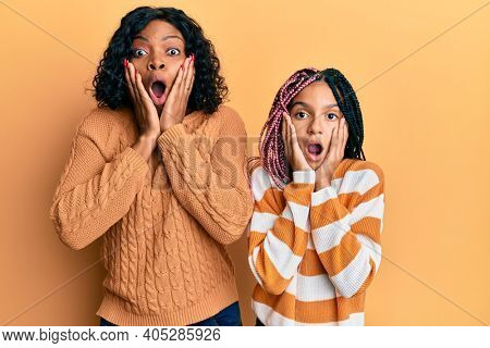 Beautiful african american mother and daughter wearing wool winter sweater afraid and shocked, surprise and amazed expression with hands on face