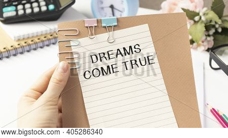 Businessman Holding A Card With Text Dreams Come True