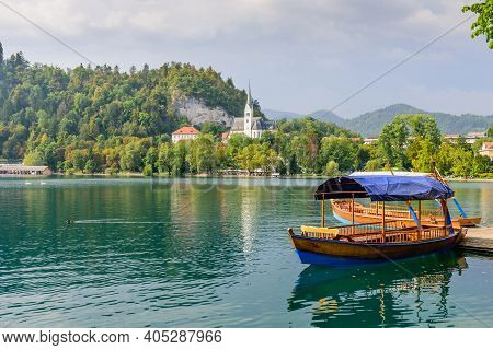 Traditional Wooden Tourist Boat On Lake Bled. Lake Bled Is A Glacial Lake In The Julian Alps In Nort