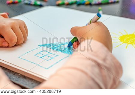 House Dream Concept. The Child Draws A House With Colored Pencils On Paper. Dreams Of Her Own Home.