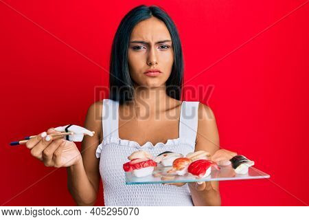 Young brunette woman eating butterfish sushi using chopsticks skeptic and nervous, frowning upset because of problem. negative person.