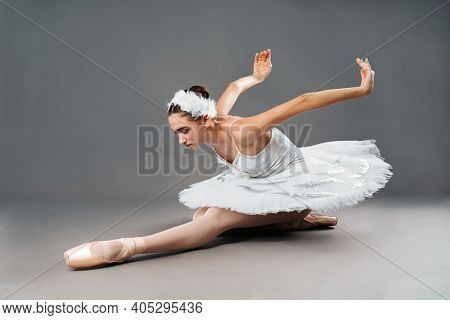 Portrait Of The Ballerina In The Role Of A White Swan On Grey Background. Beautiful, Attractive, You