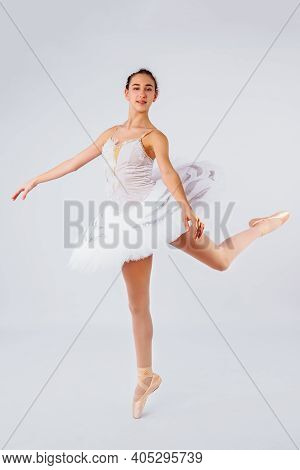 Attractive Young Ballerina With A Beautiful Body In Leotard Dancing Tiptoes In Photostudio Isolated