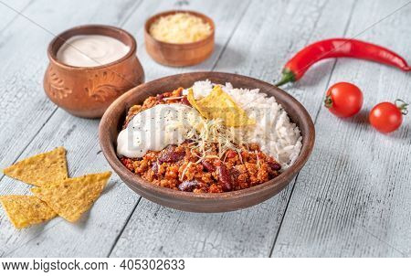 Chili Con Carne Served With Rice, Grated Cheese And Tortilla Chips