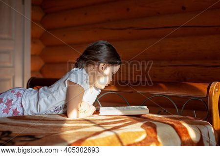 Close-up An Enthusiastic, Interested Girl Lies On Her Stomach On A Blanket On The Bed And Reads A Bo