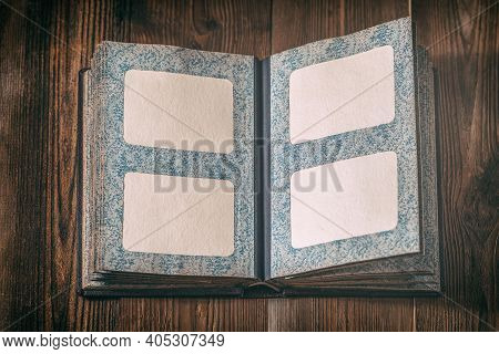 Open Old Photo Album On Dark Wooden Table. Empty Frames Inside Of An Vintage Photo Album. Copy Space