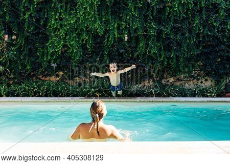 Little Boy Jumping Into A Pool. His Mom Looking Hi. Child Get Fun In The Swimming Pool Of His Home.