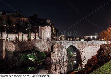 Alcantara Bridge Over Tagus River In Toledo, Spain At Night In City Lights