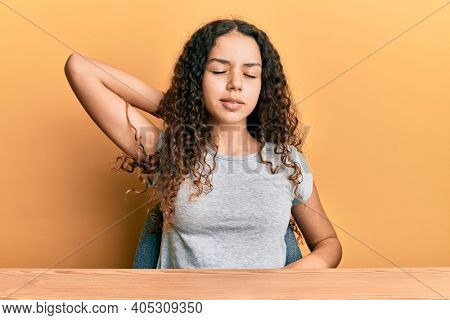 Teenager hispanic girl wearing casual clothes sitting on the table suffering of neck ache injury, touching neck with hand, muscular pain