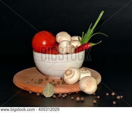 Red Tomatoes, Mushrooms, Garlic, Red Hot Pepper In A Plate, Allspice On Round Wooden Board On Dark B