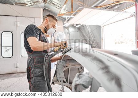 The Mechanic Works With A Grinding Tool. Sanding Of Car Elements. Garage Painting Car Service. Repai