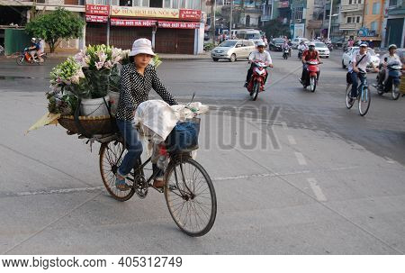 Hanoi, Vietnam- August 7 2010: Vietnamese Woman On A Bicycle Selling Flowers In The Streets Of Hanoi