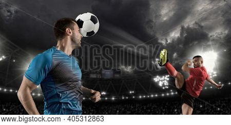 Soccer player hitting ball with head.   Football player in action on a dark arena background