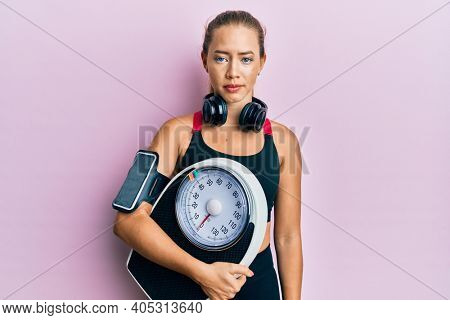 Beautiful young blonde sporty woman holding weight machine to balance weight loss relaxed with serious expression on face. simple and natural looking at the camera.