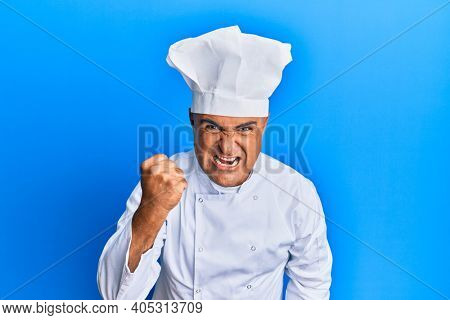 Mature middle east man wearing professional cook uniform and hat angry and mad raising fist frustrated and furious while shouting with anger. rage and aggressive concept.
