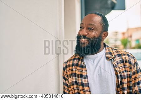 Handsome modern african american man with beard smiling positive leaning over wall