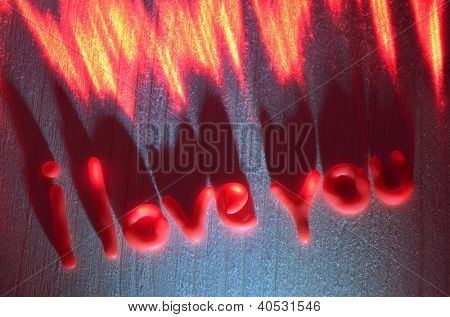 Sign of love from the polymer in the light of the laser on a wooden board