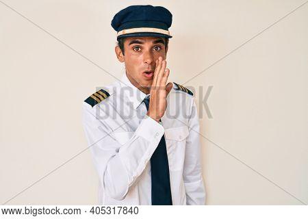 Young hispanic man wearing airplane pilot uniform hand on mouth telling secret rumor, whispering malicious talk conversation
