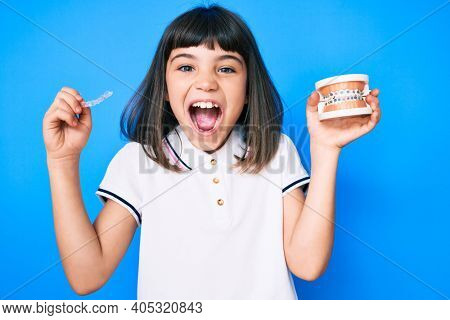 Young little girl with bang holding invisible aligner orthodontic and braces celebrating crazy and amazed for success with open eyes screaming excited.