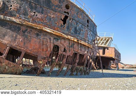 Old Rusty And Rotten Ship Wreck With Holes In Carcass, Lying On The Beach Of The Coast Line Of The S
