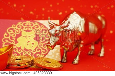 Tradition Chinese 2021 is year of the ox, Chinese characters on leftside gold ingot and coin translation:good bless for money.Chinese characters on middle mean: good bless for new year