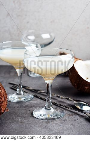 Pina Colada Liqueur In A Glass And Coconut Halves.