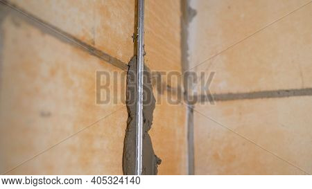 Installation Of Beacons For Leveling The Wall. Installation Of Metal Guiding Beacons For Filling And