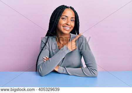 Beautiful hispanic woman wearing casual clothes sitting on the table cheerful with a smile of face pointing with hand and finger up to the side with happy and natural expression on face
