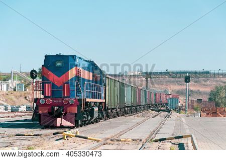 Locomotive With Container Train On Railroad Tracks At Industrial Cargo Shipment Area. Number On Fron